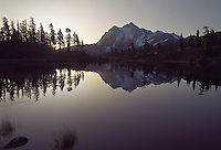 The sun rises by Mount Shuksan, mirrored on the still surface of Picture Lake. Mount Baker Wilderness, North Cascades Mountain Range, Washington State.