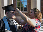 Tanner Sauter gets help with his cap from Shalleeah Smith before the University of Nevada College of Business and Division of Health Sciences graduation ceremony on Friday morning, May 19, 2017.