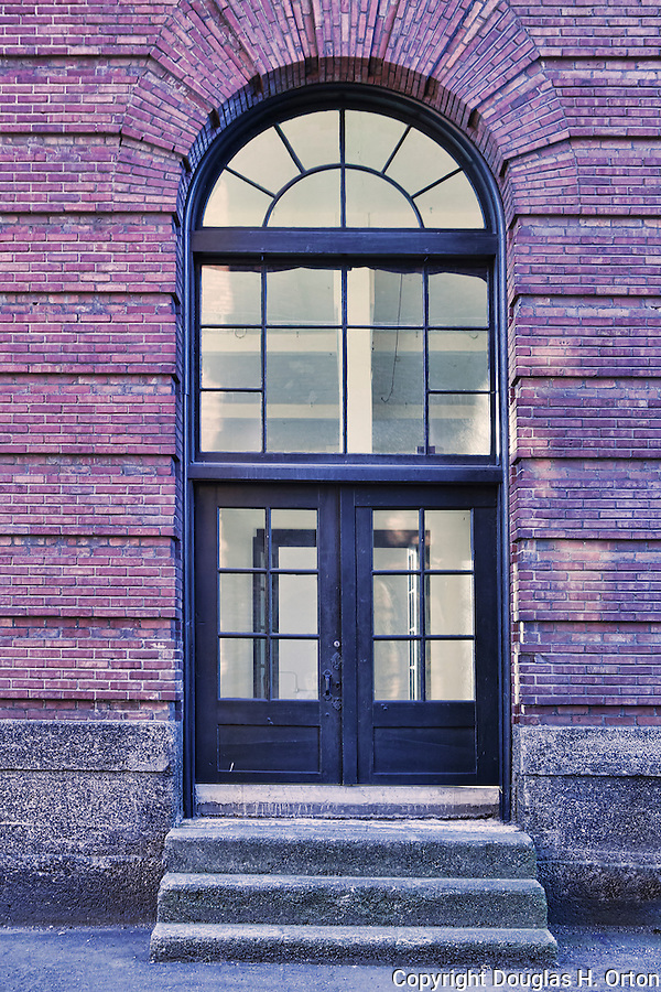 Arched brick doorway in vacant old building.  Georgetown neighborhood, Seattle, WA.  Red brick, arched glass, empty lighted hallway, concrete stairs.