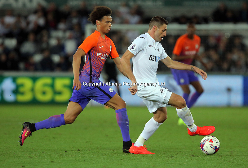 Angel Rangel of Swansea City (R) is closely followed Leroy Sane of Manchester City during the EFL Cup Third Round match between Swansea City and Manchester City at The Liberty Stadium in Swansea, Wales, UK. Wednesday 21 September.