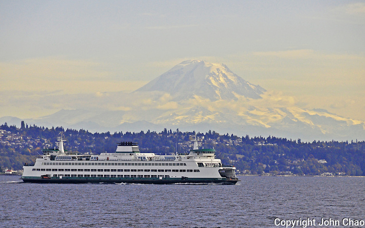 A Washington State Ferry crosses Puget Sound past Alki Point Lighthouse and with Mount Rainer as backdrop.