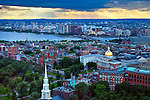 The famous gold dome of the Massachusetts State House in the capital city of Boston, MA. The Charles River and the city of Cambridge are in the background, and the steeple of the historic Park Street Church in the foreground.