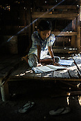 A young girl studies for her examinations in her house in Kwin Sekhan Villagein Pyapon district of Myanmar.