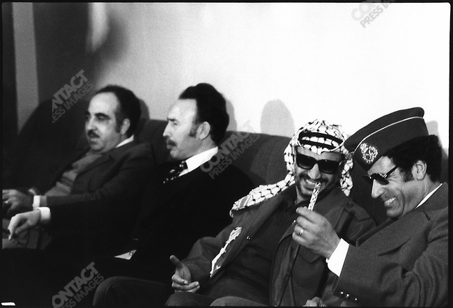 Muammar el-Qaddafi (r) and PLO chairman Yasir Arafat (second from right) share a laugh during the Triploi Summit, held in December 1977