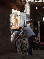 A man selling paintings sets up his stall in the morning in the Old City, Damascus, Syria