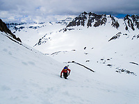 A climber in the San Juan Mountains of Colorado traverses steep slopes on the flanks of 14,157 foot high Mt.Sneffels as 13,700 foot high Gilpin Peak rises in the background.