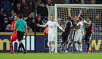A scuffle breaks out between Robert Huth of Leicester City and Ashley Williams of Swansea (R) after the first pushed over Lukasz Fabianski of Swansea during the Barclays Premier League match between Swansea City and Leicester City at the Liberty Stadium, Swansea on December 05 2015