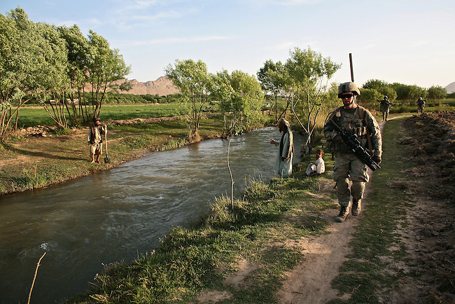 Two farmers talk across a canal as  soldiers from Company B, 2nd Battalion, 508th Parachute Infantry Regiment walk past them while on patrol in the Arghandab valley near Kandahar, Afghanistan. March 27, 2010.    DREW BROWN/STARS AND STRIPES