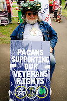 Pagan advocate age 60 carrying sign supporting veterans rights in parade. MayDay Parade and Festival. Minneapolis Minnesota USA