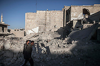 In this Tuesday, Oct. 08, 2013 photo, Syrian residents walk in front of a demolished building instants after a warplane hit a residential area in Maraat Al-Nouman in the Idlib province countryside of Syria. (AP/Photo)