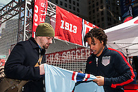 Former men's national team player Cobi Jones autographs a jersey for a fan during the centennial celebration of U. S. Soccer at Times Square in New York, NY, on April 04, 2013.