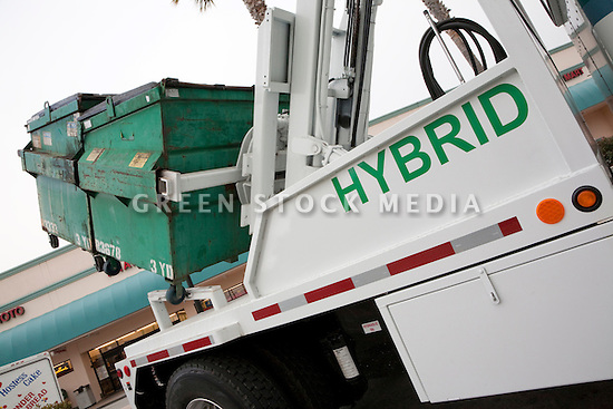 Tilted view of a Peterbilt Hybrid Electric (HE) Truck Model 330 Class 6 vehicle. This particular vehicle is being used by South San Francisco Scavenger Company for garbage and recycling bin pick up. Using a hybrid rather than a rather than regular diesel engine saves money on fuel and reduces emissions. It is hauling two 3 yard garbage bins on the hydraulic lift they installed on the truck bed. California, USA