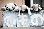 Three teddy bears are lined up on the balcony of a shop selling dried fish and squid in Shimoda, Japan.