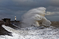Waves crash against the promenade wall of the Porthcawl lighthouse, caused by Storm Freya in south Wales, UK. Sunday 03 March 2019