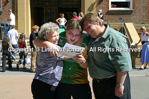 """Happy student with proud parents receiving his """"A"""" Level results at a Further Education College."""