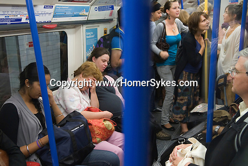 Pregnant woman tired and exhausted. London Underground passengers. UK