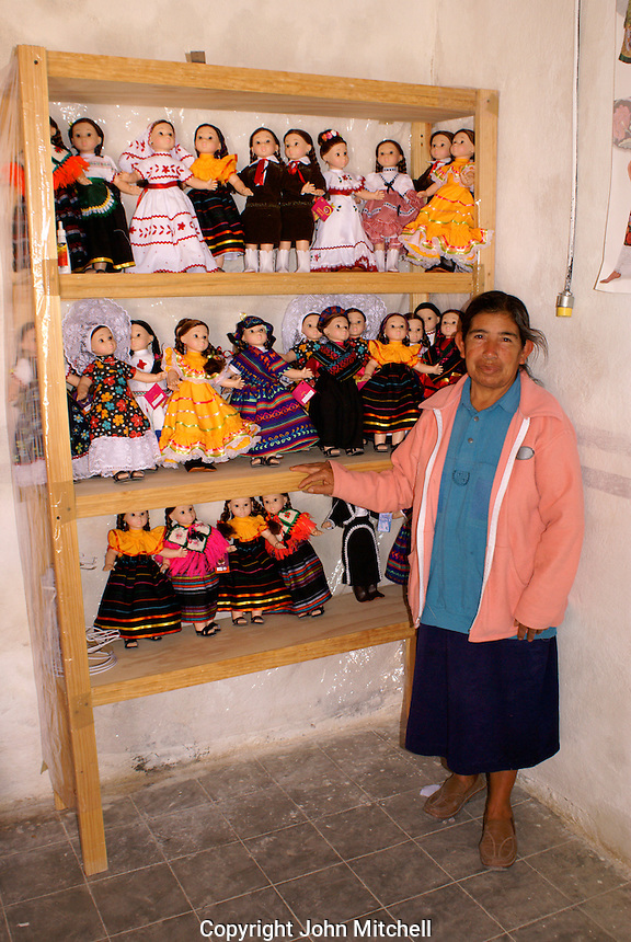 Nacinta Najera standing next to dolls wearing traditional Mexican regional costumes, Manos Creativas cooperative,  Mineral de Pozos, Guanajuato, Mexico.