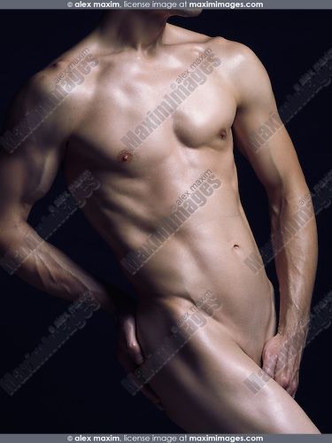 Young nude man with fit shiny naked body isolated on black background