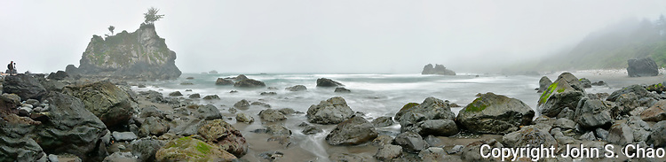 Panorama of rocky Hidden Beach in moody fog with a photographer, Redwood National and State Parks, Klamath, California