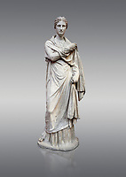 Ancient Greek funerary statue of a women, type Small Herculaneum Woman style. From Delos circa 2nd Cent BC. Athens National Archaeological Museum. Cat No 1827. Against grey<br /> <br /> This marble statue from Delos shopws a women wearing a full length chiton and a himation that covers her entire body and arms. This style of statue is known os 'Small Herculaneum Woman' and is a copy of a famous original dating from 300 BC.