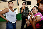 Pathe waits with other migrants from Honduras at a bus terminal in Tapachula. As they have lunch, fried chicken and Pepsi, they figure out which minibus to take. The bus terminal is a dusty parking lot where dozens of minibuses pick up passengers..