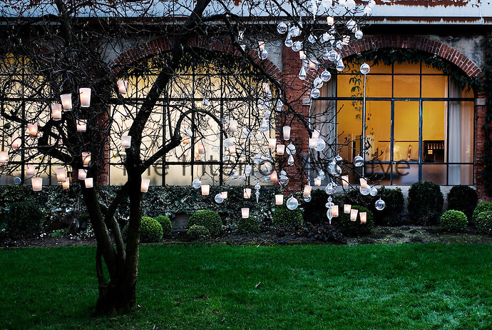 A tree in the garden decorated with glass baubles and tealights has become an alternative Christmas tree