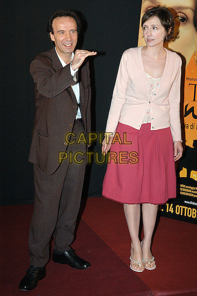 "ROBERTO BENIGNI & NICOLETTA BRASCHI .Photocall of the movie ""La tigre e la neve"".October 4th, 2005.Ref: OME.full length pink cardigan skirt black suit .www.capitalpictures.com.sales@capitalpictures.com.© Capital Pictures."