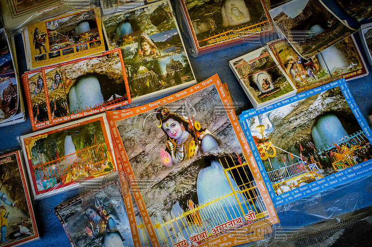 Posters and memorabilia of Hindu God Shiva and the Shivalingam is sold in the makeshift stall at the base of Amarnath Cave in Kashmir. Hindu pilgrims brave sub zero temperatures and high altitude passes and make their pilgrimage to reach the sacred Amarnath cave, which houses a lingam - a stylized phallus, worshipped by Hindus as a symbol of God Shiva.