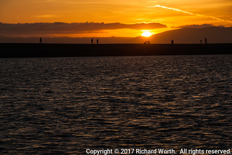 As if pulling the covers over its head, the sun slides past the Santa Cruz Mountains at sunset viewed from the eastern shore of San Francisco Bay.