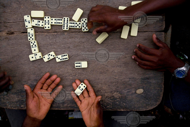 Men play a game of dominos on the island of Limones.