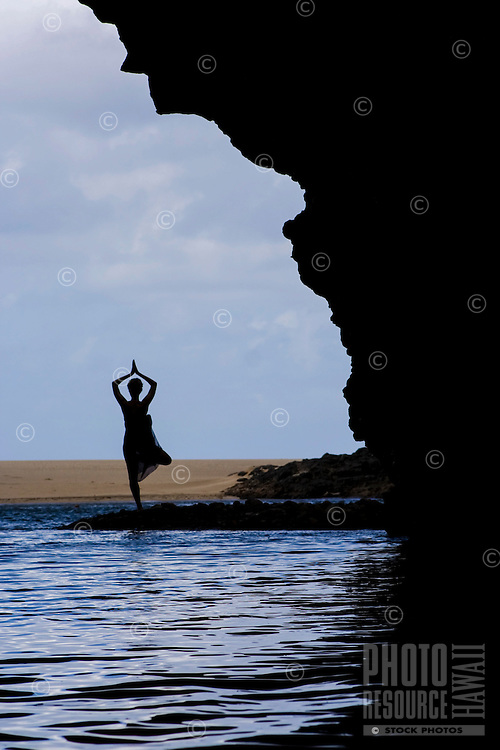 A silhouetted woman does yoga in a sea cave at Kalalau Beach, Na Pali Coast, Kaua'i.