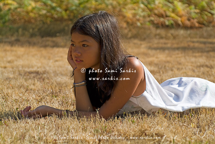 Young Asian girl lying down in a field near Landes Forest, France.