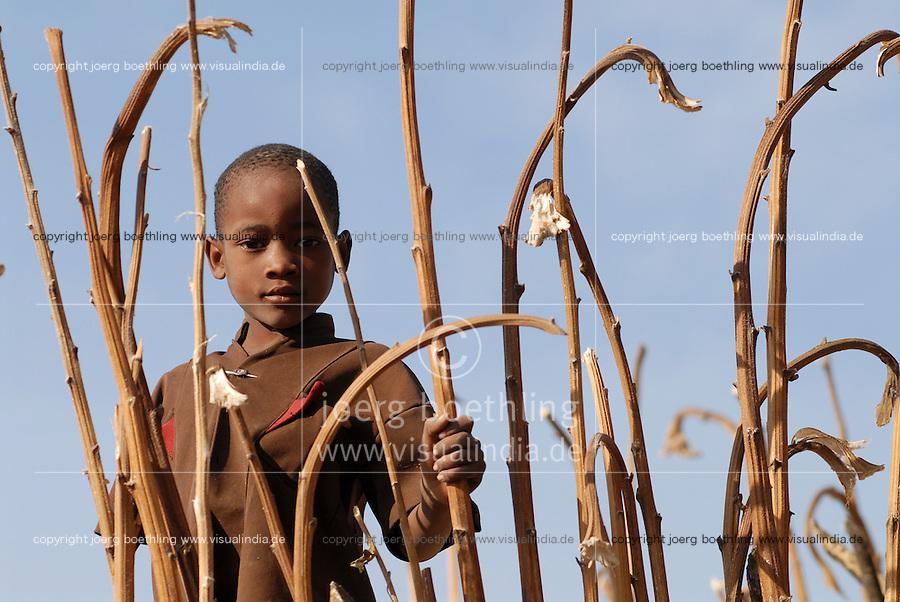 TANZANIA , young boy looking through dried plant  in village in Meatu district / TANSANIA , Junge schaut durch vertrocknete Pflanzenstengel in einem Dorf in Meatu