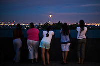 People look at the super moon and the World Trade Center from a state park in New Jersey, June 23, 2013, Photo by Eduardo Munoz Alvarez / VIEWpress.