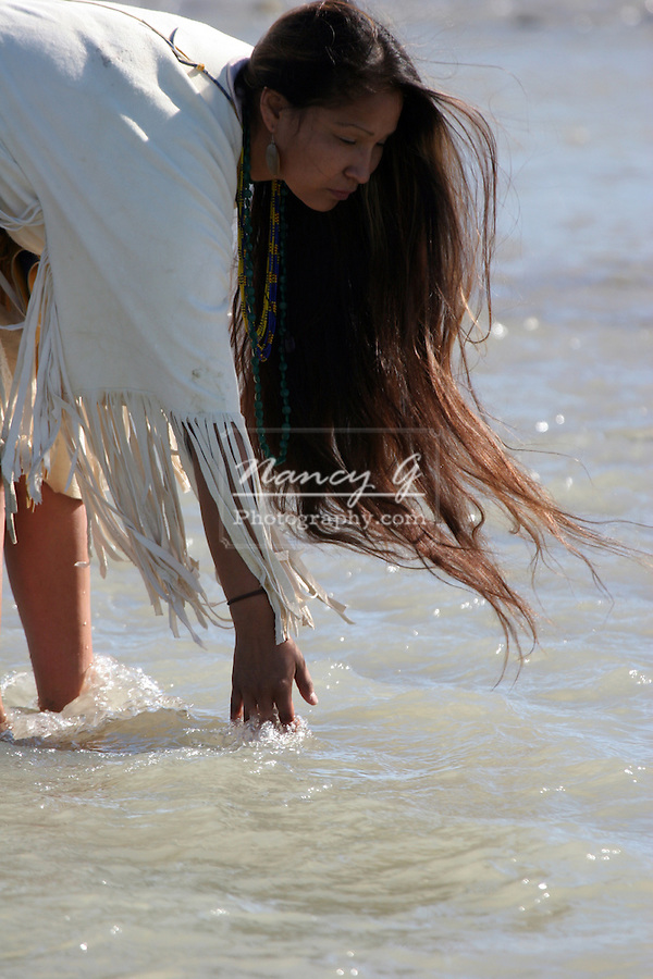 A Native American Indian women bending over touching the river water in South Dakota