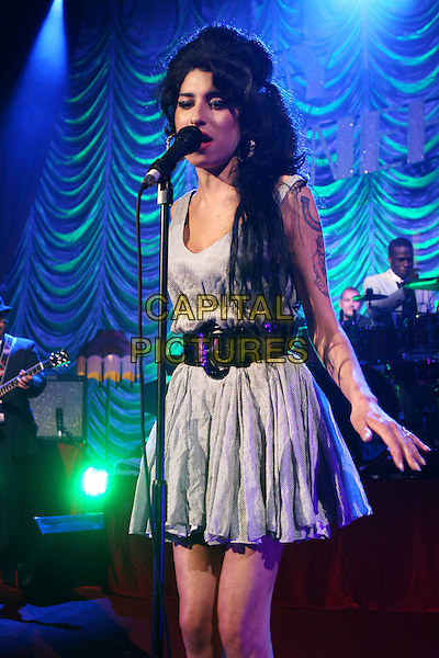 AMY WINEHOUSE.Live in concert at the Shepherd's Bush Empire, London, England..May 28th, 2007.gig performance music half length 3/4 grey gray dress back belt singing .CAP/MAR.© Martin Harris/Capital Pictures.