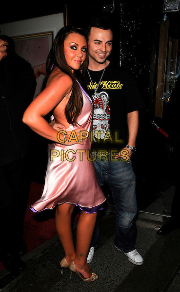 "MICHELLE SCOTT-LEE & ANDY SCOTT-LEE.Andy Scott-Lee's new single ""Unforgettable"" party, Embassy club, London, England..February 5th, 2008.full length heaton pink satin silk dress purple trim gold shoes jeans denim black t-shirt tee married husband wife tattoo hand on hip.CAP/CAN.©Can Nguyen/Capital Pictures"