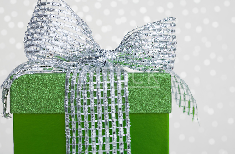 Studio shot of green gift with ribbon on sparkled background
