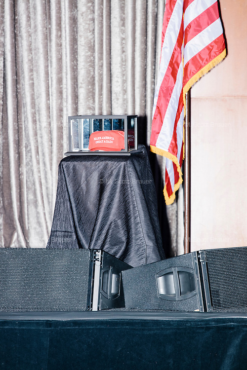 "A ""Make America Great Again"" hat rests in a display case on stage in the ballroom at the Midtown Hilton Hotel in New York, New York, on the morning of election day, Tues., Nov. 8, 2016. Republican nominee Donald Trump held his election night rally at the hotel."
