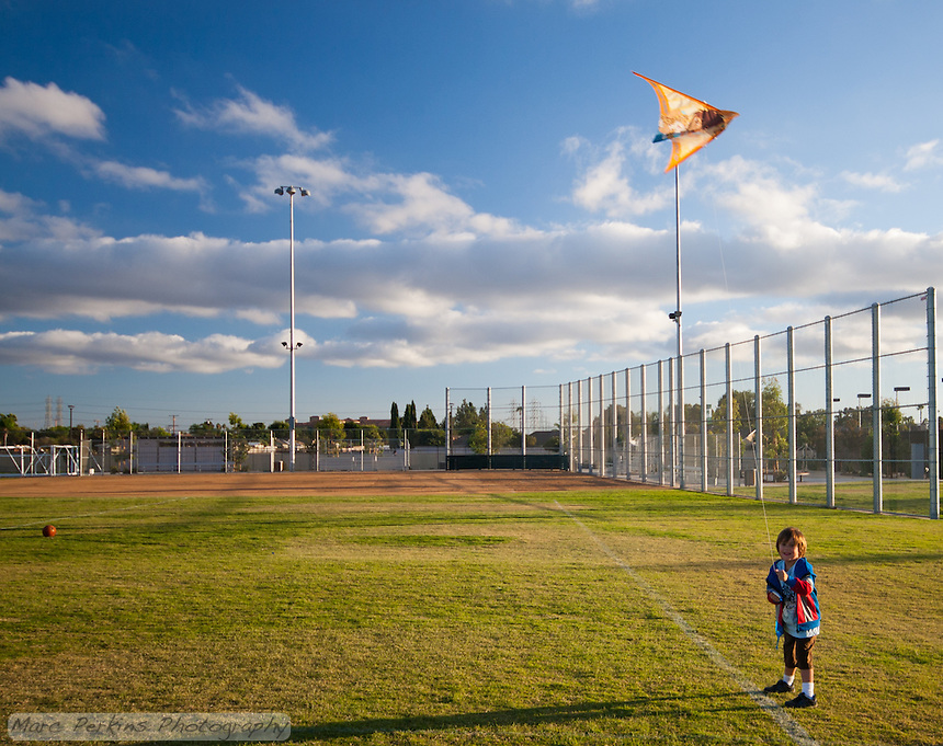 A boy happily looks at the camera while flying a kite on the baseball field at Stanton Central Park.