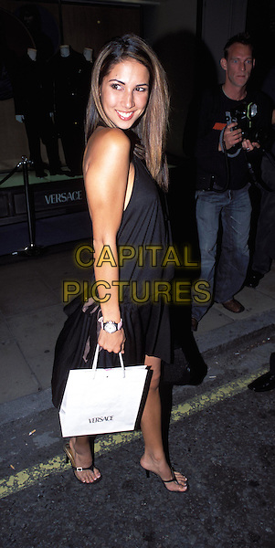 LEILANI.outside Versace shop.goody bag, goodie bag, shopping bag, designer, full length, full-length, little black halterneck dress, sandals.www.capitalpictures.com.sales@capitalpictures.com.© Capital Pictures.