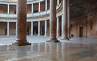 Patio in the Palace of Charles V, designed by Pedro Machuca in the 16th century in Renaissance style as a residence for the Holy Roman Emperor in the Alhambra, Granada, Andalusia, Southern Spain. The circular patio has 2 levels with a lower Doric colonnade and an upper Ionic colonnade. The Alhambra was begun in the 11th century as a castle, and in the 13th and 14th centuries served as the royal palace of the Nasrid sultans. The huge complex contains the Alcazaba, Nasrid palaces, gardens and Generalife. Granada was listed as a UNESCO World Heritage Site in 1984. Picture by Manuel Cohen