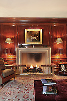 A fire burns in the hearth of an early 20th century inspired  panelled saloon, surrounded by comfortable armchairs and subdude lighting