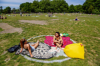ROTTERDAM - sunbathing in the park during Ascension Day. Special one and a half meter circles to help people keep their distance from each other. In the Vroesenpark, Het Park at the Euromast and the Kralingse Bos, Stadsbeheer has made circles with which you can clearly define your own 'aura' so that other people do not get too close.