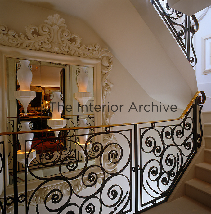 A collection of ceramic vases is displayed against a mirror in an ornate plasterwork frame on the staircase landing