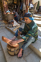 Fes, Morocco.  Place Seffarine.  Craftsman Hammering a Copper Bowl into Shape.