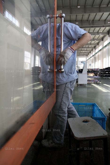 A employee at Ning bo Xuelong Group Co. operates a plastic molding machine that makes cooling fans for Geely Automobile in Ningbo, China, on 26 March, 2008.