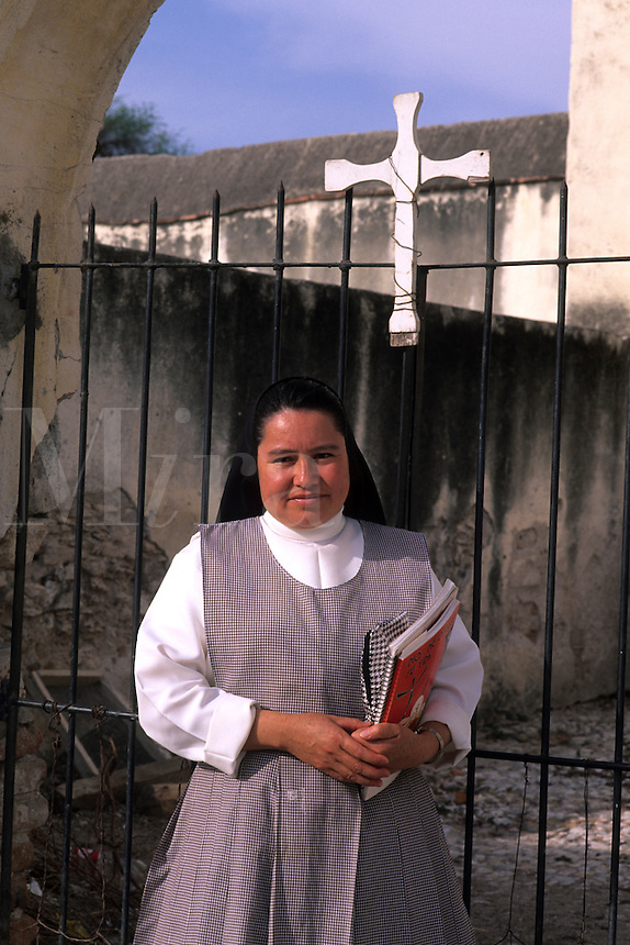 Portrait of Catholic nun in front of cross in town square in San Miguel de Allende Mexico .