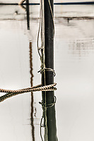 Mooring pole with a ships rope photographed up close, with the shadow from a ship mast mirroring in the sea.