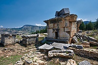 "Picture of Tomb Tomb 114 ""tomb of curses"" of the North Necropolis. Hierapolis archaeological site near Pamukkale in Turkey.<br /> <br /> TOMB 114 (Second half of the 2nd century AD) <br /> <br /> The tomb lies on the left hand side of the road and is enclosed by a perimeter wall; it rests on a base withifiree steps, with a bench piked(1 front of it. Inside are three beds and the ossuary. On the roof, a sarcophagus, broken as result of an <br /> earthquake, bears an inscription mentioning the occupant Aelios Apollinarios and his wife Neratia Apollonis. On the facade is an inscription of great interest which refers to the punishment inflicted on those who violate the sepulchre: as well as the usual fines, it invokes diseases, misfortunes and punishments in the next world. This inscription has led to the building being named the Tomb of the Curses."